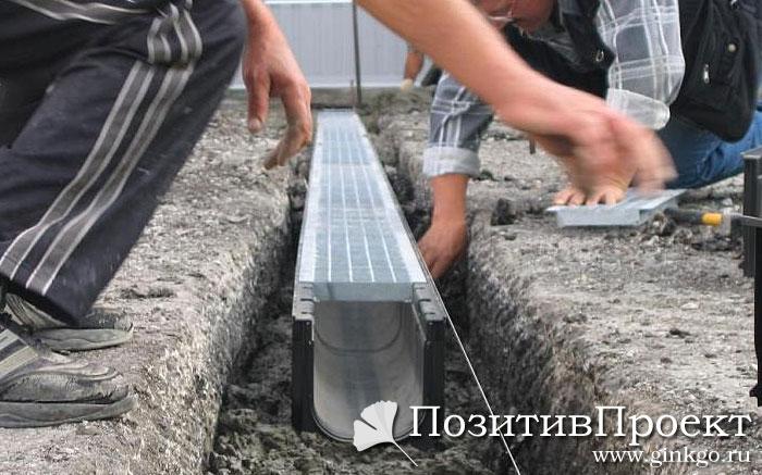 Рабочие укладывают лотки ливневой канализации